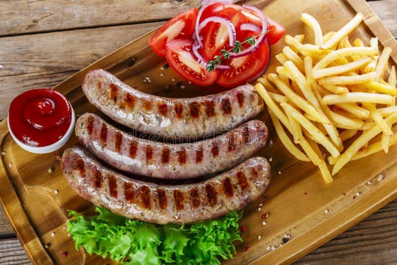 Salsichas grelhadas com fritadas francesas fotos de stock royalty free