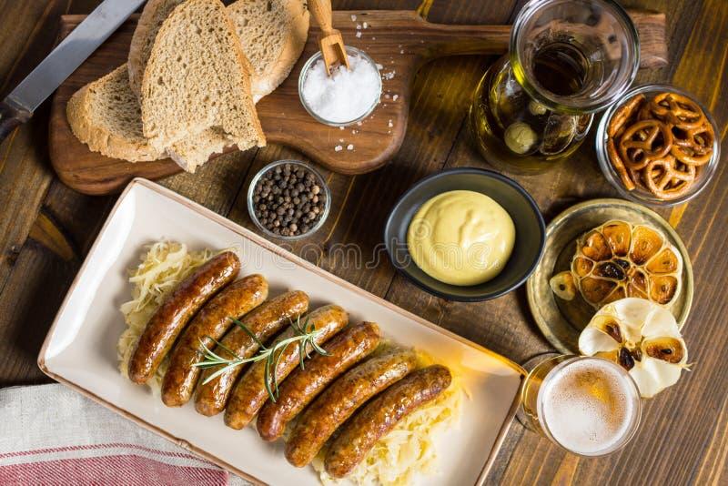 Salsichas grelhadas com salada, mostarda e cerveja de couve imagens de stock