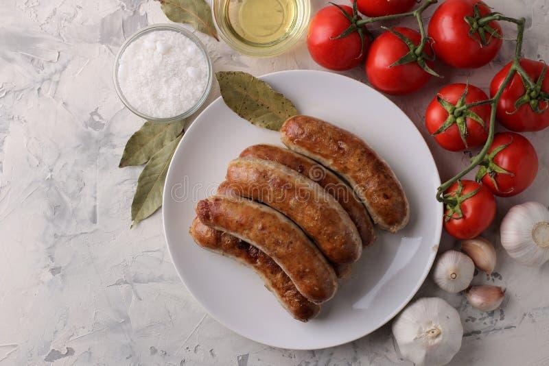 Salsichas grelhadas com tomates, óleo de girassol e alho em um fundo claro Vista superior imagens de stock