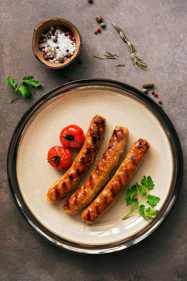 Salsichas grelhadas com tomates e especiarias em uma placa em um fundo r?stico marrom Vista superior, configura??o lisa imagem de stock royalty free