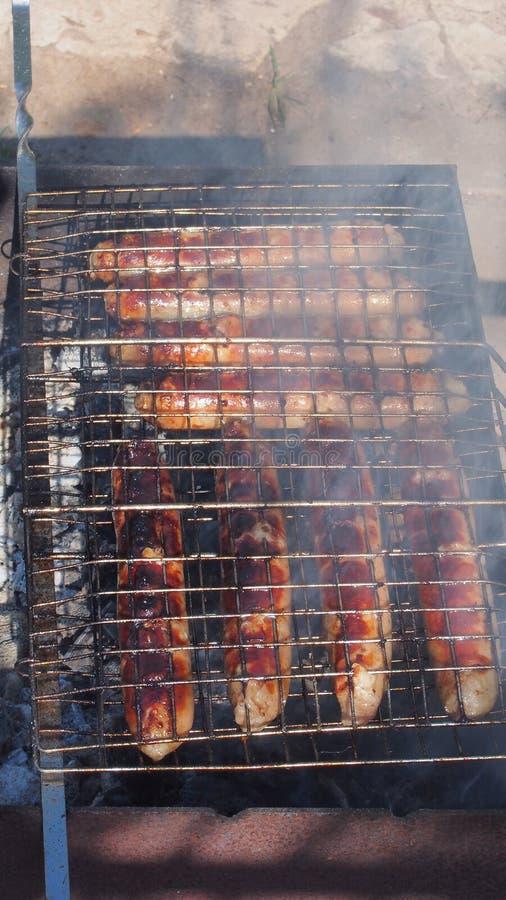 Salsichas grelhadas, cozinhadas na grade barbecue imagem de stock