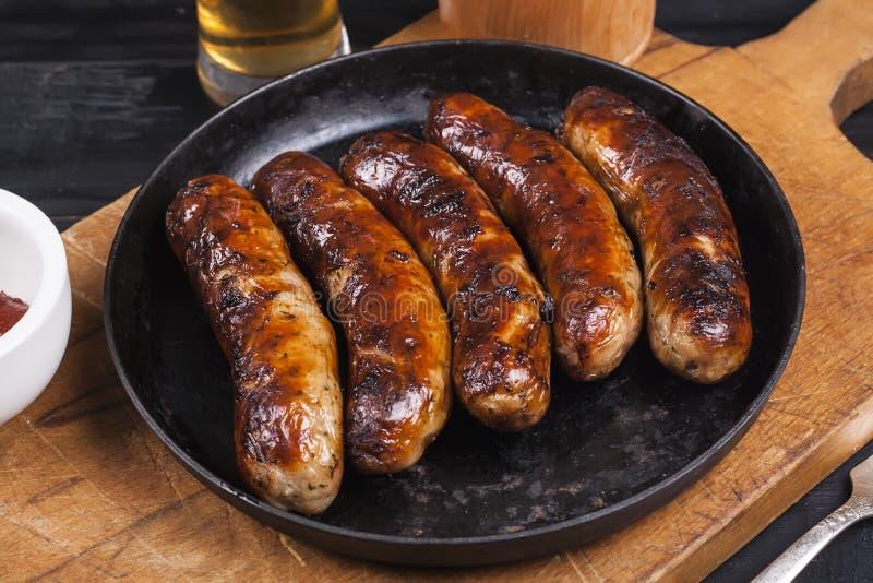Salsichas grelhadas suculentas da galinha em um fundo de madeira escuro foto de stock