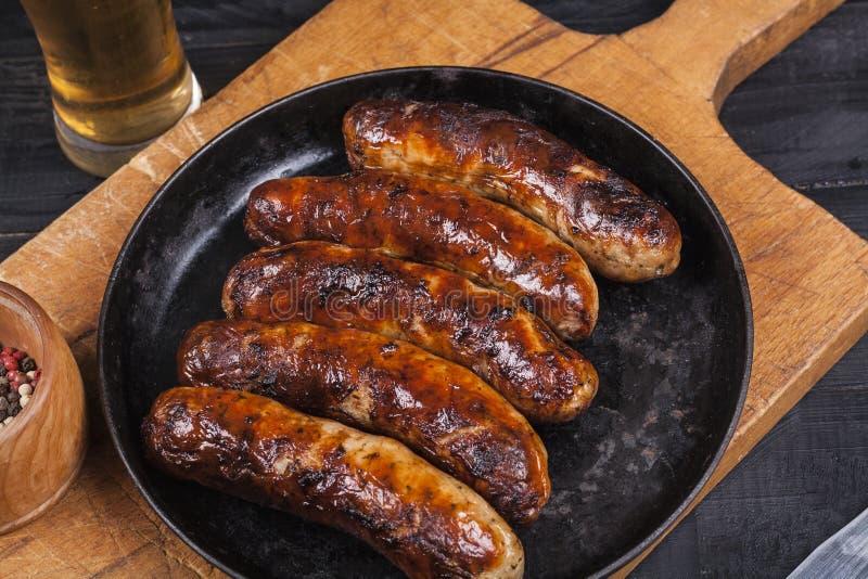 Salsichas grelhadas suculentas da galinha em um fundo de madeira escuro imagens de stock