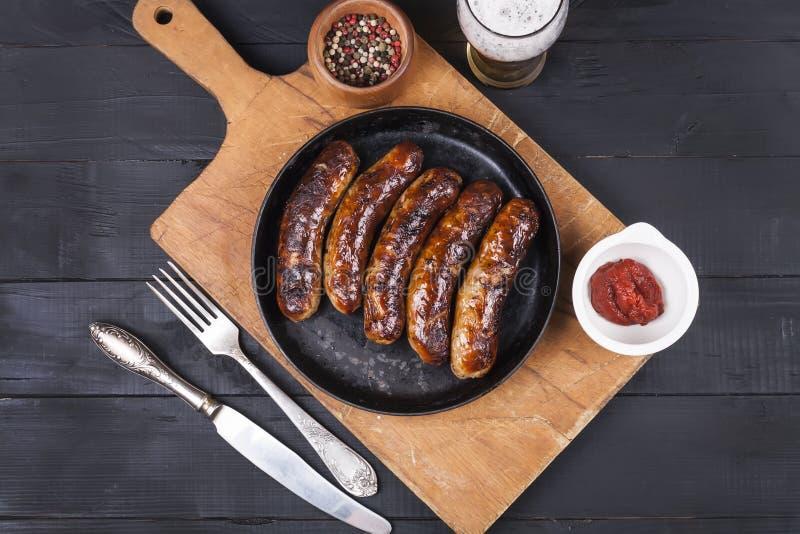Salsichas grelhadas suculentas da galinha em um fundo de madeira escuro imagem de stock royalty free