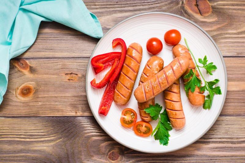 Salsichas grelhadas, tomates frescos, pimentas e salsa em uma placa em uma tabela de madeira fotografia de stock