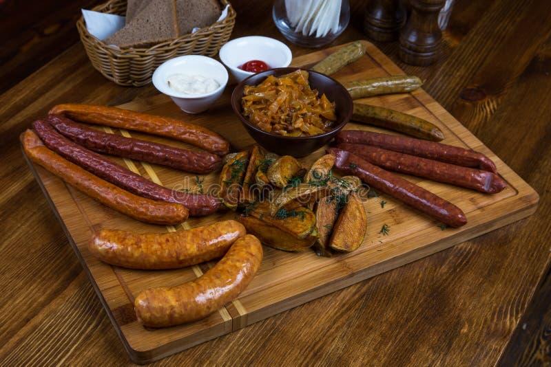 Salsichas quentes da variedade que servem na placa de madeira foto de stock royalty free