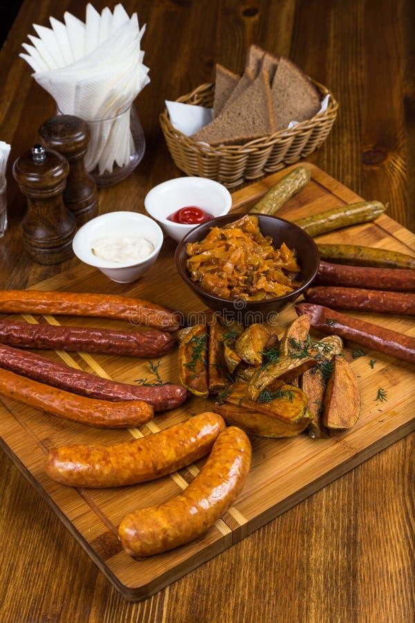 Salsichas quentes da variedade que servem na placa de madeira foto de stock