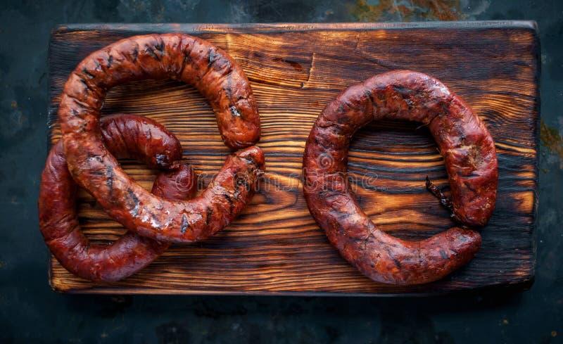 Salsichas redondas fumados da carne do anel na placa de madeira fotografia de stock