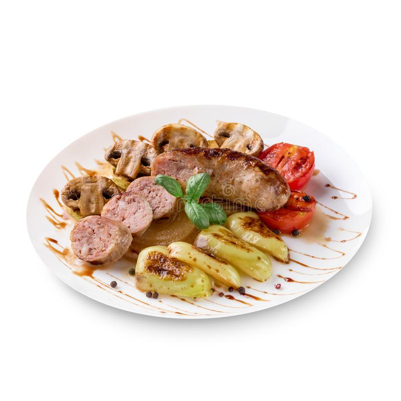 Salsichas Roasted com molho e vegetais de tomate em um fundo branco fotografia de stock