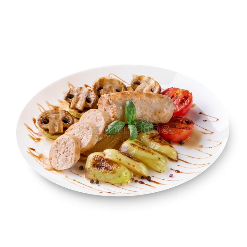 Salsichas Roasted com molho e vegetais de tomate em um fundo branco imagens de stock royalty free