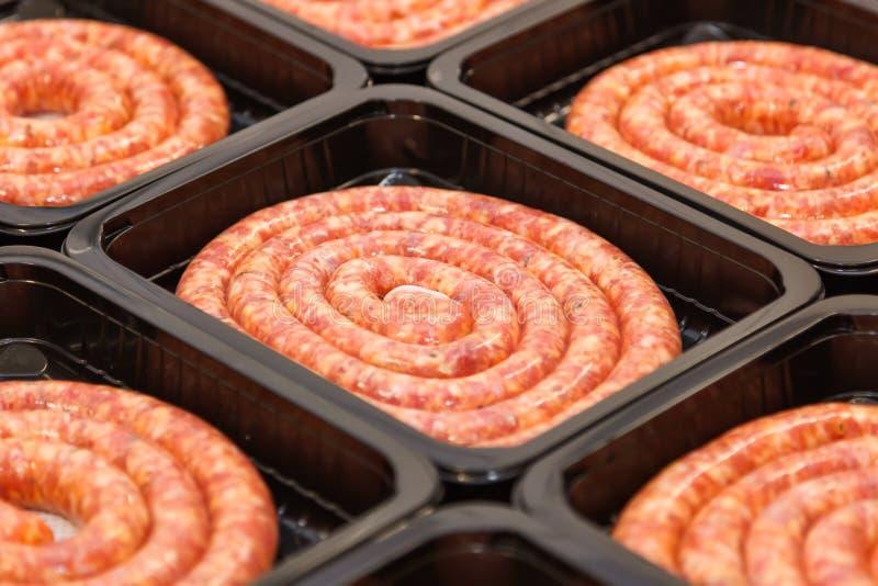 Salsichas roladas da carne crua na caixa de embalagem fotos de stock