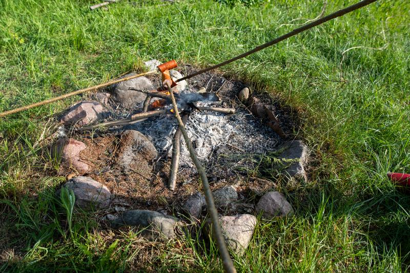 Salsichas saborosos que gotejam com a gordura cozida em um fogo aberto Uma chaminé em um jardim da casa fotos de stock royalty free