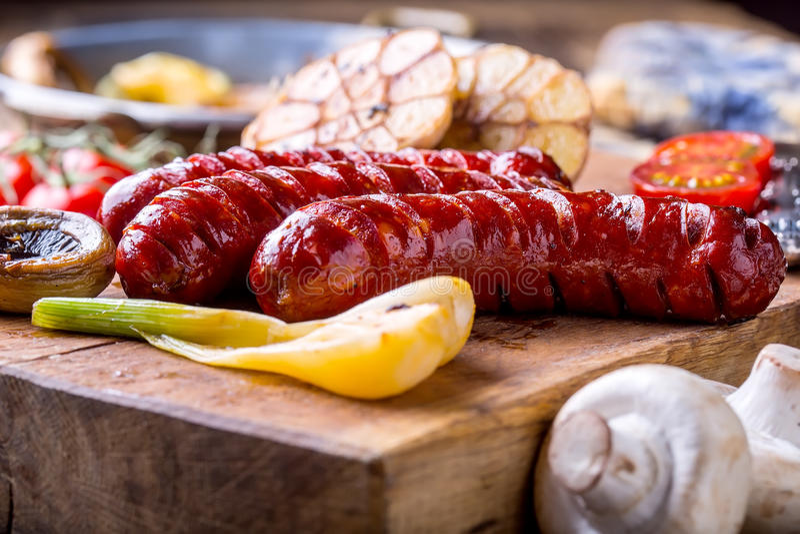 Salsichas Salsichas da grade Salsicha grelhada com os tomates e as cebolas do alho dos cogumelos foto de stock
