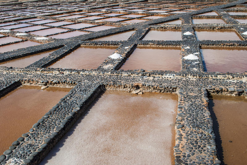 Salt evaporation pond. The seawater or brine is fed into large ponds and water is drawn out through natural evaporation which allows the salt to be subsequently stock photo
