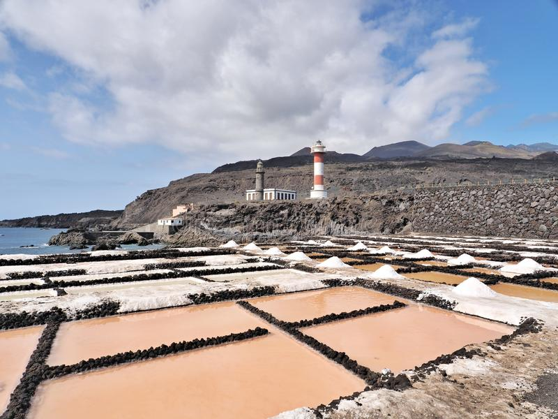 Salt extraction with the pink in a lava landscape on La Gomera, overlooking the red and white striped lighthouse salt pans stock photography