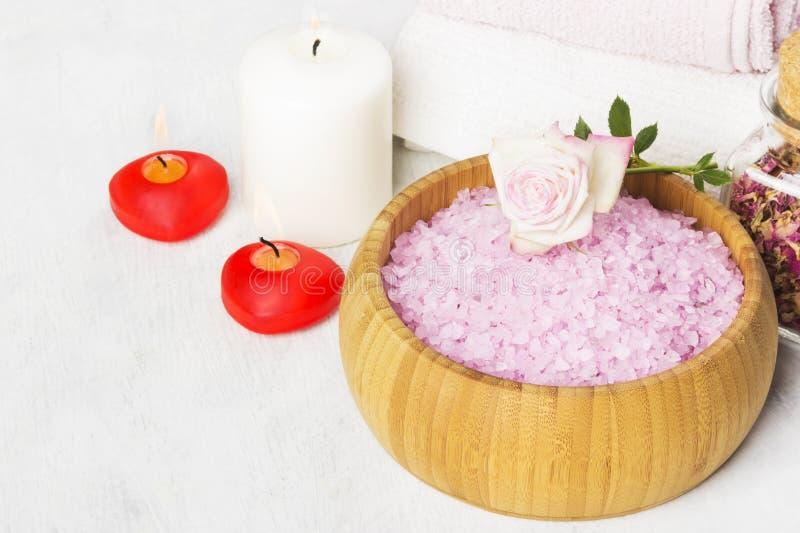 Salt för bad med arom av en ros i en träbunke, kronblad och en fr arkivfoto