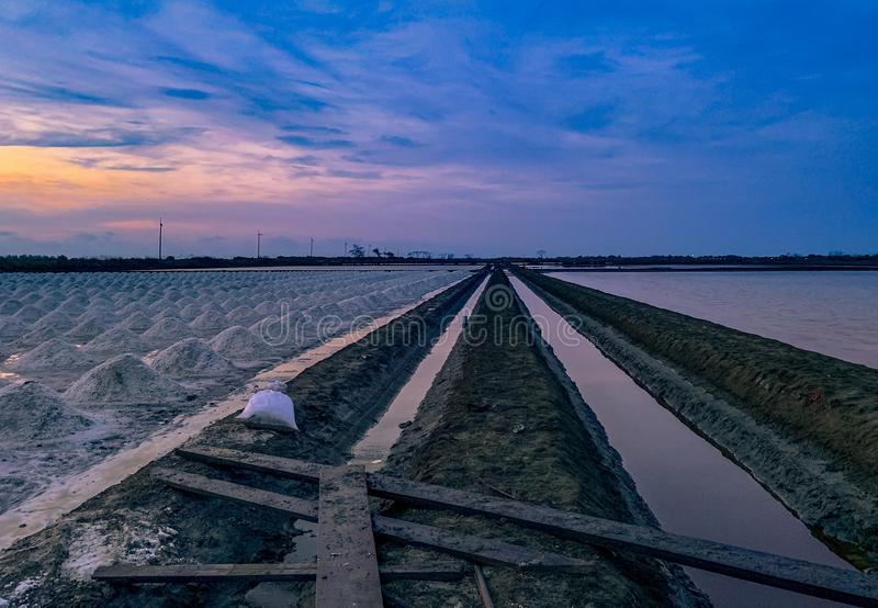 Salt farm in the morning with sunrise sky and clouds. Landscape of sea salt field in Thailand. Sea water in canal and soil pathway. In farm. Raw material of stock image