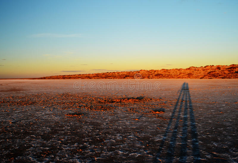 Salt Lake at Sunset. Long shadows of a couple on the dry surface of a salt lake at sunset royalty free stock photo