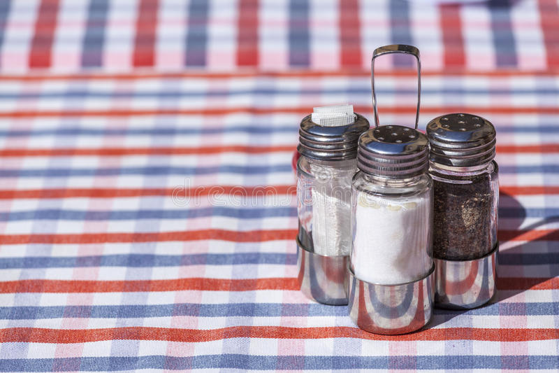 Salt, peppar- och tandpetareuppsättning över en utomhus- restaurangtabell royaltyfria bilder