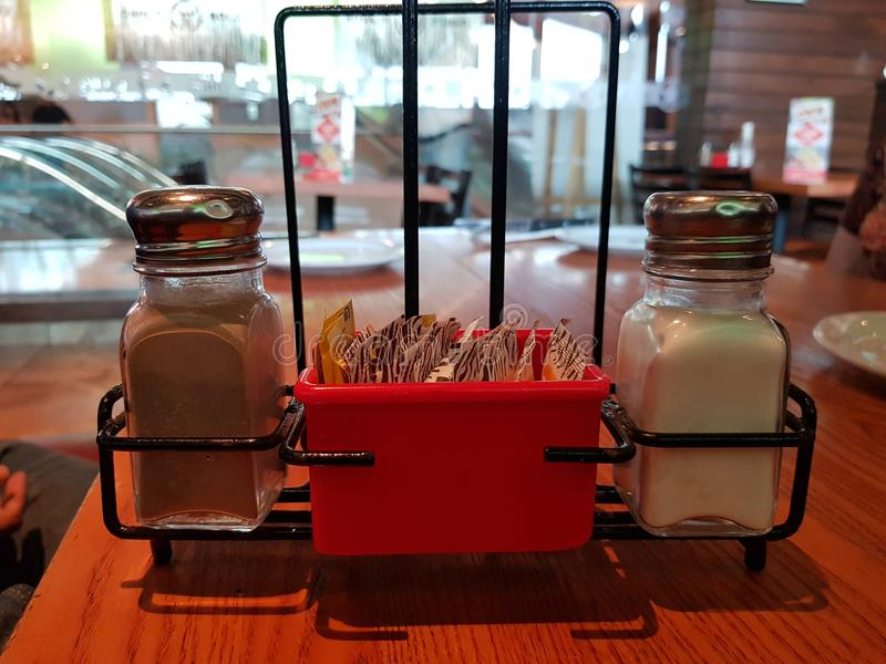 Salt and pepper container on a table in a restaurant stock images