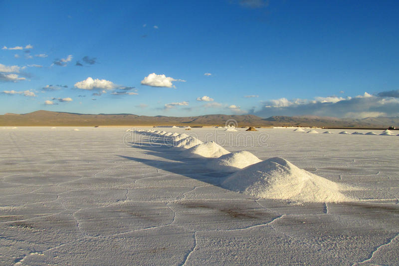 Salt piles on Salar. Salt lake plato, flat plaine covered with white salt and blue water. Mountains on horizont. Uyuni Salar, Bolivia. Altiplano in South royalty free stock images