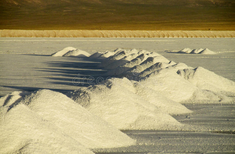 Salt piles on Salar. Salt production. Salt lake plato, flat plaine covered with white salt and blue water. Mountains on horizont. Uyuni Salar, Bolivia stock photos