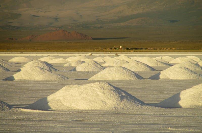 Salt piles on Salar at sunset. Salt piles on Salar, salt production. Salt lake plato, flat plaine covered with white salt and blue water. Mountains on horizont stock photos