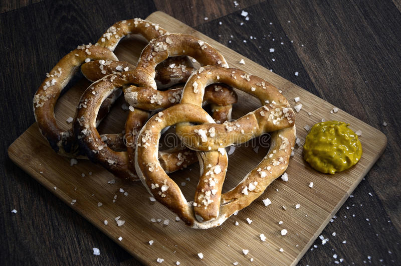Salt Pretzels and Mustard on Rustic Dark Wood Table. Salt sprinkled giant pretzels snacks served on a wooden board with mustard, set on a rustic dark wooden royalty free stock images