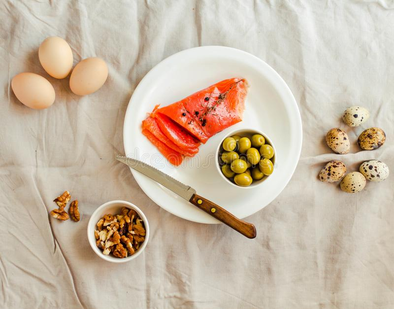 Salt Salmom with quail eggs, nuts and olive on a white linen tablecloth background. Top view. Paleo diet. Healthy high protein and stock photos