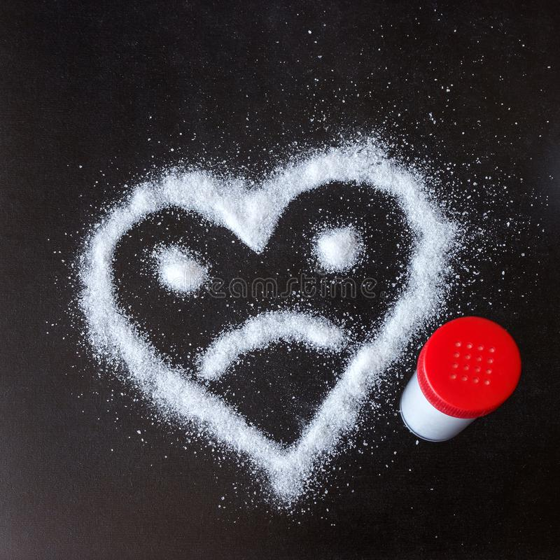 Salt scattered on black surface. Drawn heart with a sad face. Concept- diet, harm to health from excessive consumption of salt and sugar stock photo