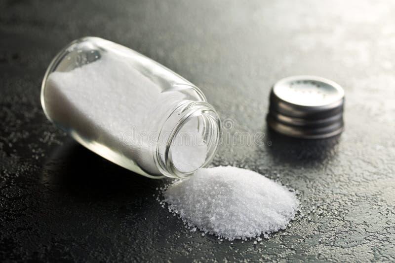Salt shaker. On black kitchen table royalty free stock photography