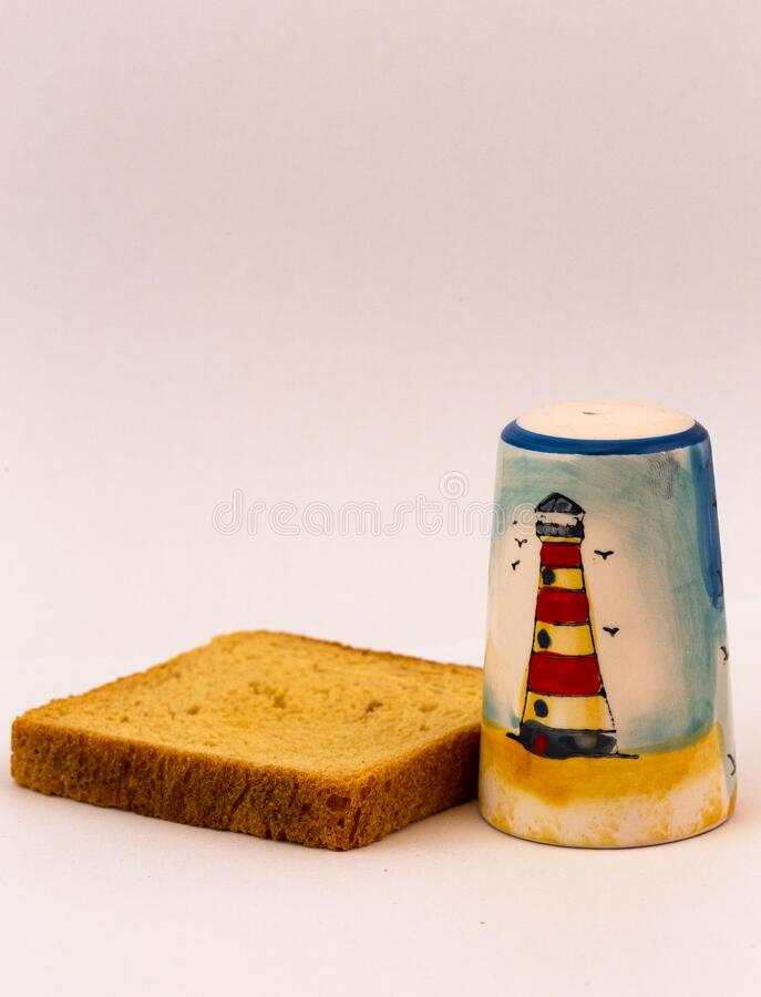 Salt shaker and slice of bread. For welcome in Serbia. Salt and bread. Beautiful salt shaker with lighthouse picture royalty free stock images