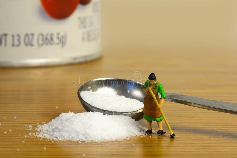 Salt Spill. Little lady sweeping up spilled salt royalty free stock image