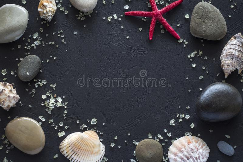 Salt and stones with a starfish on a black background is laid out in the form of a frame. Copy space royalty free stock photo