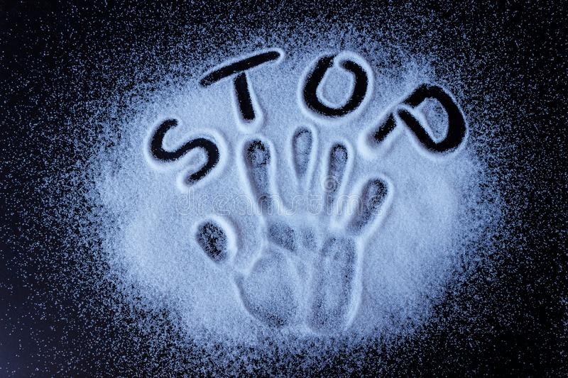 Salt, sugar, scattered on black surface. Written word- stop and handprint. stock photo