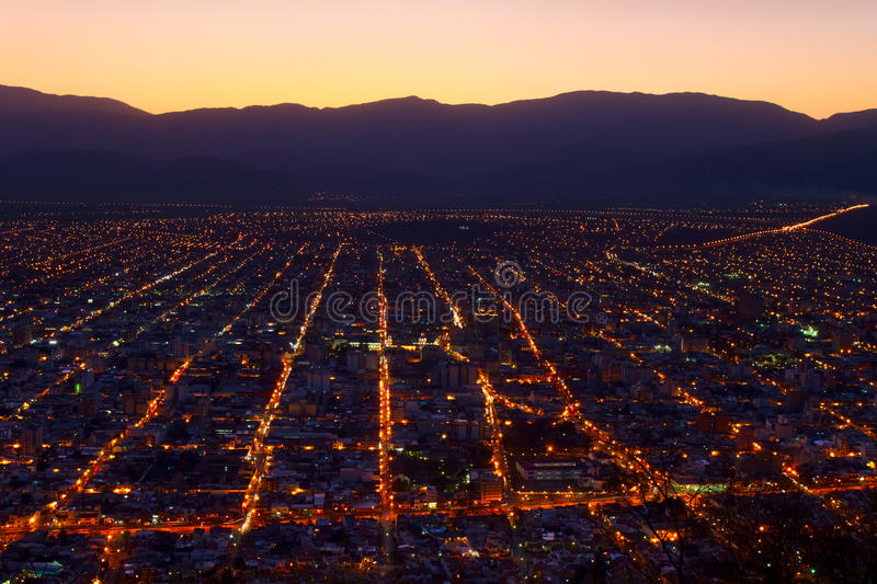 Salta at Dusk. Panoramic view of Salta, Argentina, at the turn from dusk to night, as seen from Cerro San Bernardo hill. There are some tree branches in the royalty free stock images