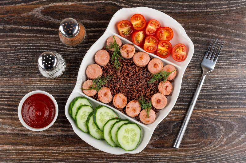 Salta och peppra, ketchup, delad maträtt med stekte stycken av korvar, röda ris, gurkor, tomaten, gaffel på tabellen Top beskådar royaltyfri foto