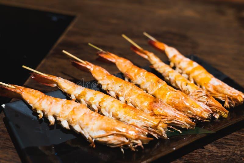 Saltade grillade räkasteknålar, tjänade som på maträtt i japansk restaurang för Izakaya stilstång Japan havs- aptitretaremeny royaltyfri bild