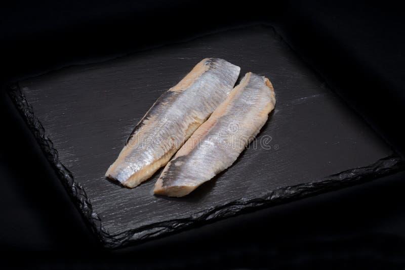 Saltade utan ben filéer av denfångade atlantiska sillen som ordnas på den naturliga svarta stenen Clupeaharengus fotografering för bildbyråer