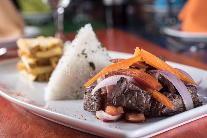 Saltado peruano del lomo de la comida: Una carne de vaca salada con los tomates, cebolla, frió las patatas y el arroz imagen de archivo