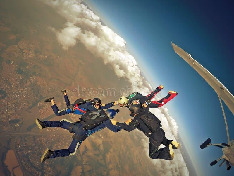 Saltando em queda livre a formação de quatro vias da equipe fotografia de stock