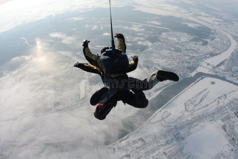 Saltando em queda livre o salto em tandem do plano na perspectiva da terra imagens de stock
