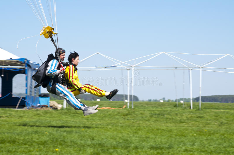 Saltando em queda livre terras em tandem na grama de um avião L-410 fotografia de stock royalty free