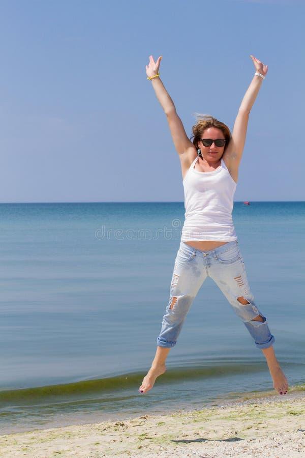 Saltando a la mujer feliz en la playa, quepa al cuerpo atractivo sano deportivo en tejanos, mujer goza del viento, libertad, vaca fotos de archivo