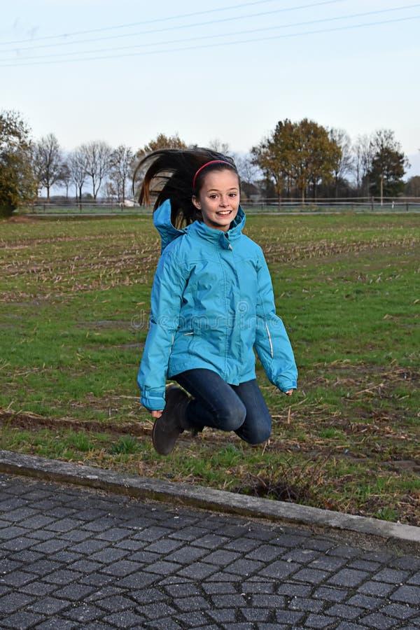 Saltando para a alegria, adolescente feliz foto de stock royalty free