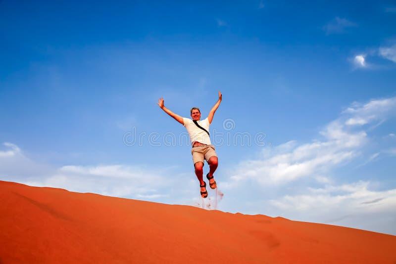 Saltando su sulle dune di sabbia immagine stock