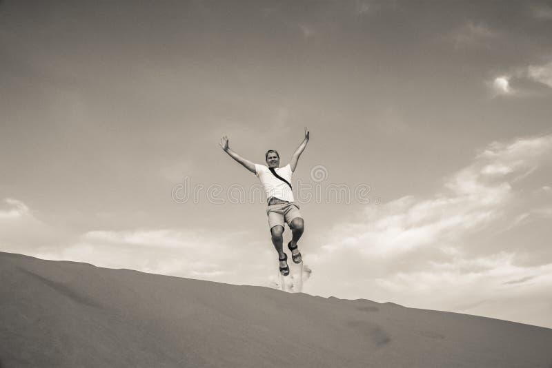Saltando su sulle dune di sabbia fotografia stock libera da diritti