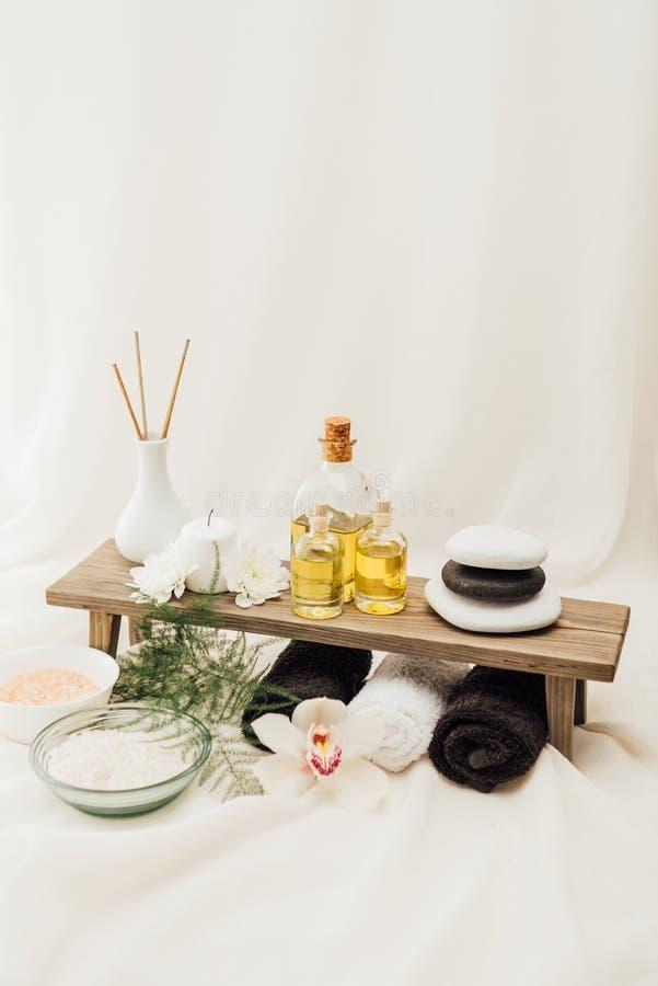 saltar den övre sikten för slutet av ordningen av brunnsortbehandlingtillbehör med orkidéblomman, handdukar, olja och arkivfoto