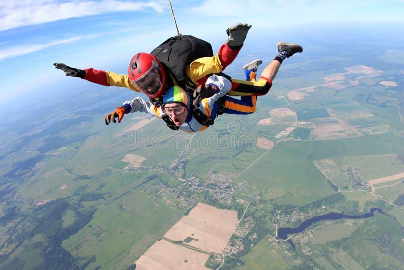 Saltar em queda livre em tandem A mulher e o instrutor estão voando no céu fotografia de stock royalty free