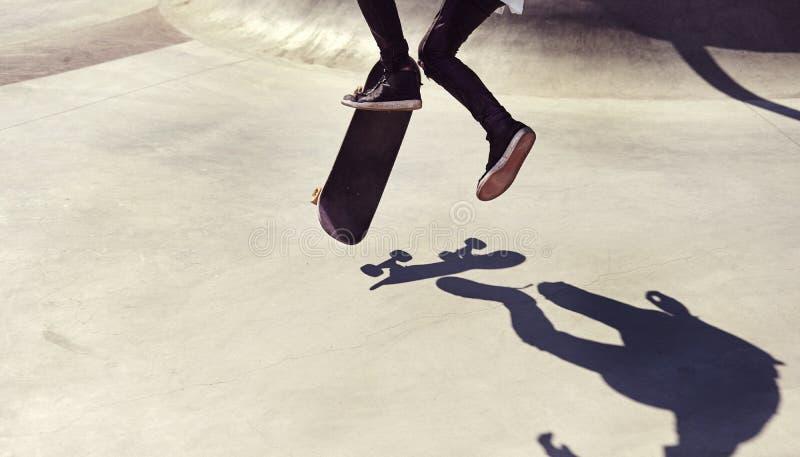 Salte el truco en el parque, deporte del skater del extremo del estilo libre de la práctica imagen de archivo